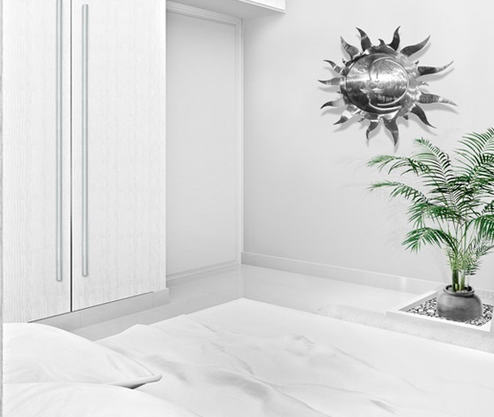 White themed hotel room with plant at foot of bed